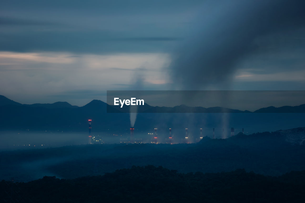 mountain, cloud - sky, sky, scenics - nature, environment, smoke - physical structure, beauty in nature, no people, mountain range, nature, pollution, building exterior, architecture, environmental issues, built structure, outdoors, emitting, silhouette, industry, air pollution