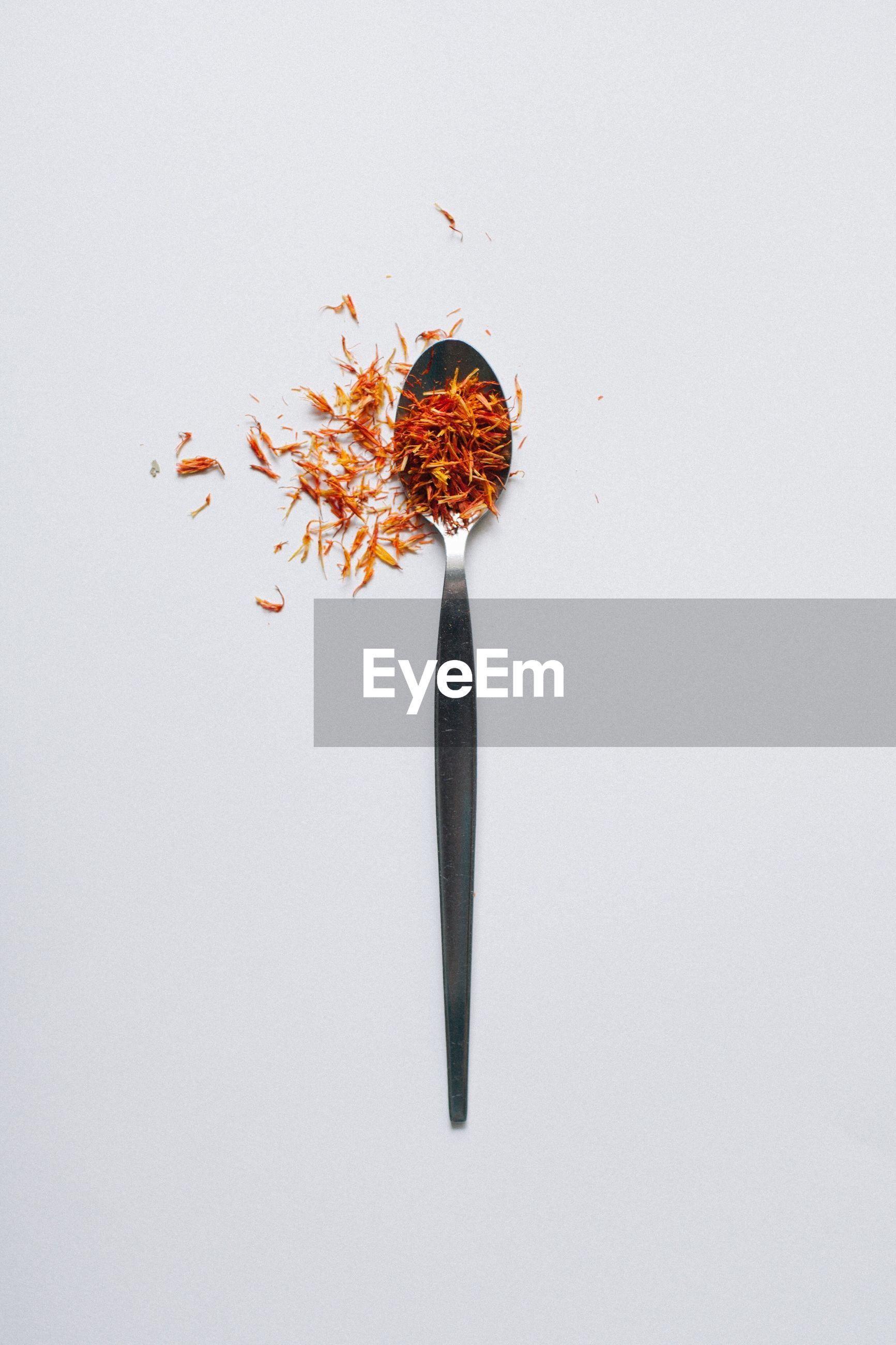 High angle view of ingredient in spoon against white background