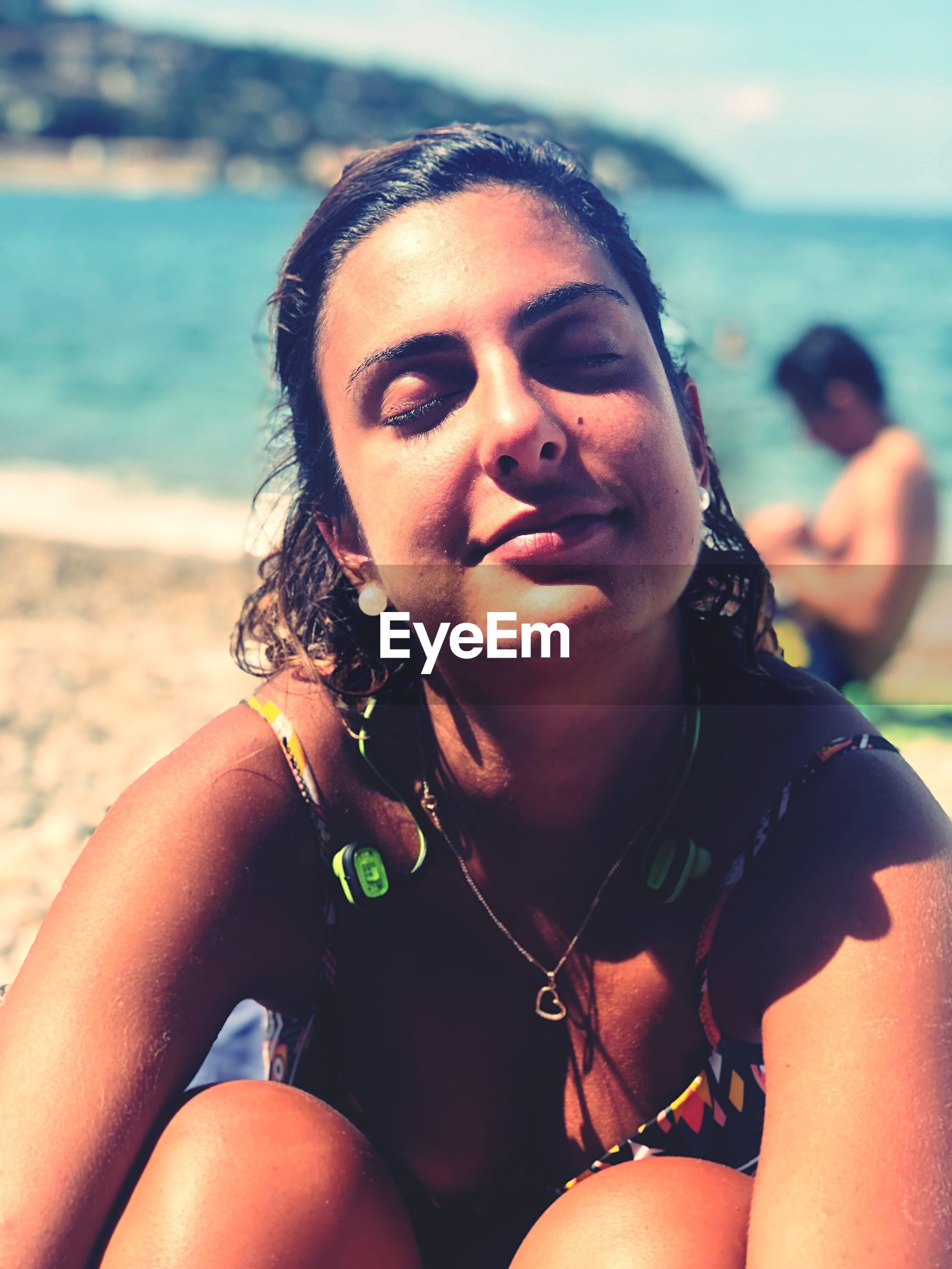 Young woman with eyes closed sitting at beach