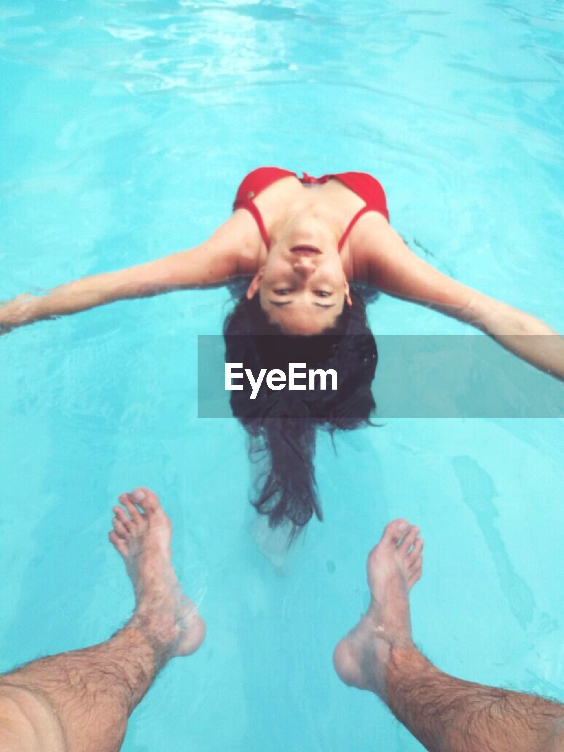 swimming pool, water, leisure activity, swimming, real people, fun, happiness, summer, enjoyment, high angle view, day, smiling, two people, outdoors, wet, vacations, shirtless, portrait, lifestyles, togetherness, young adult, young women, people