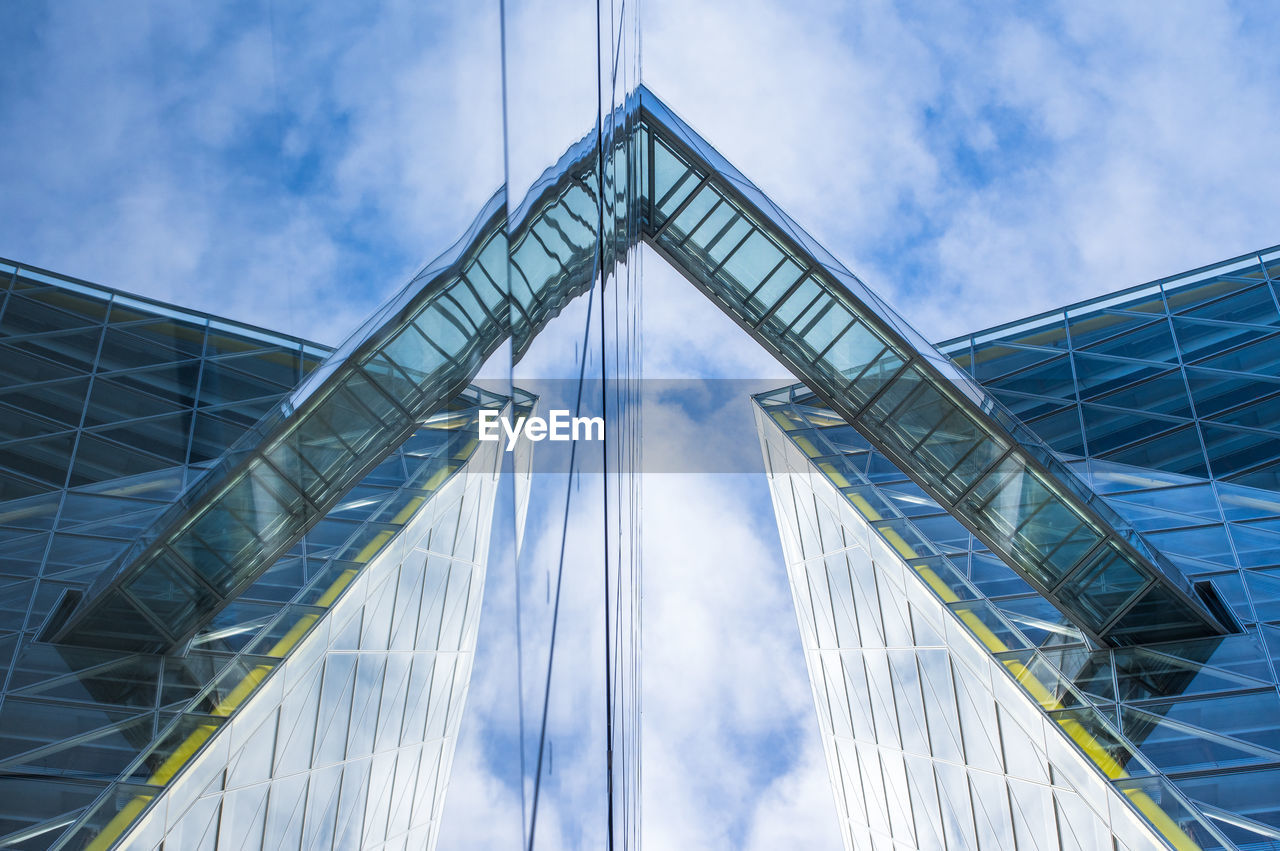 cloud - sky, sky, architecture, built structure, low angle view, glass - material, building exterior, modern, nature, day, city, no people, building, office building exterior, outdoors, connection, office, tall - high, skyscraper, reflection, directly below