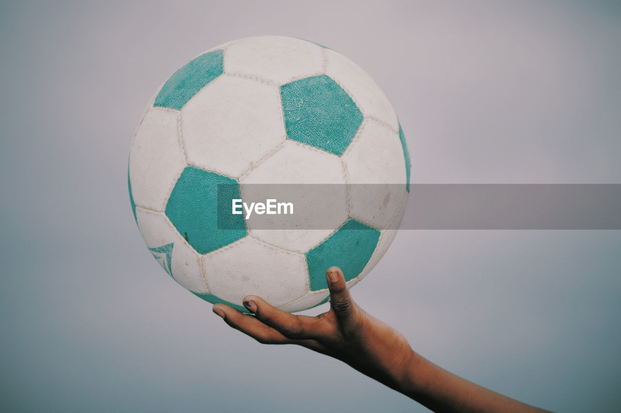 Cropped hand holding ball against sky