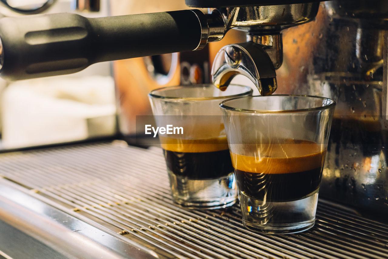 Espresso in glass below coffee maker at cafe