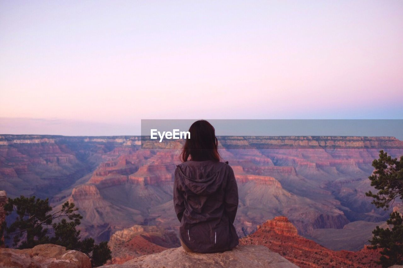 Rear View Of Woman Sitting On Cliff Against Grand Canyon During Sunset