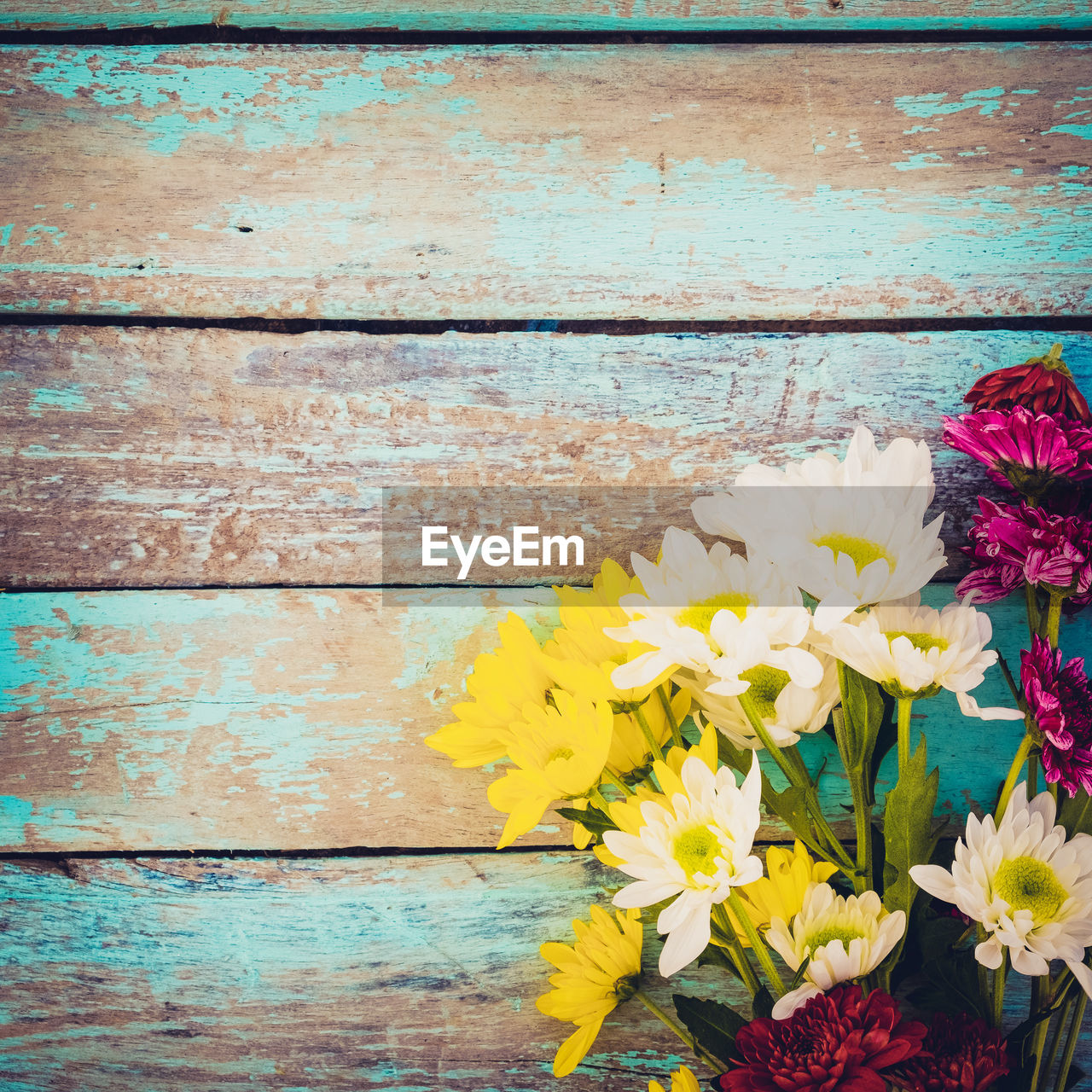 flowering plant, flower, plant, vulnerability, yellow, fragility, freshness, wood - material, petal, flower head, beauty in nature, multi colored, inflorescence, nature, close-up, no people, day, wall - building feature, outdoors, directly above, flower arrangement, bouquet