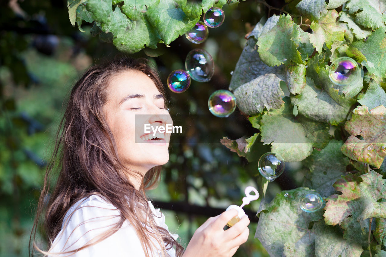 Smiling Young Woman Holding Wand By Bubbles Blowing In Mid-Air