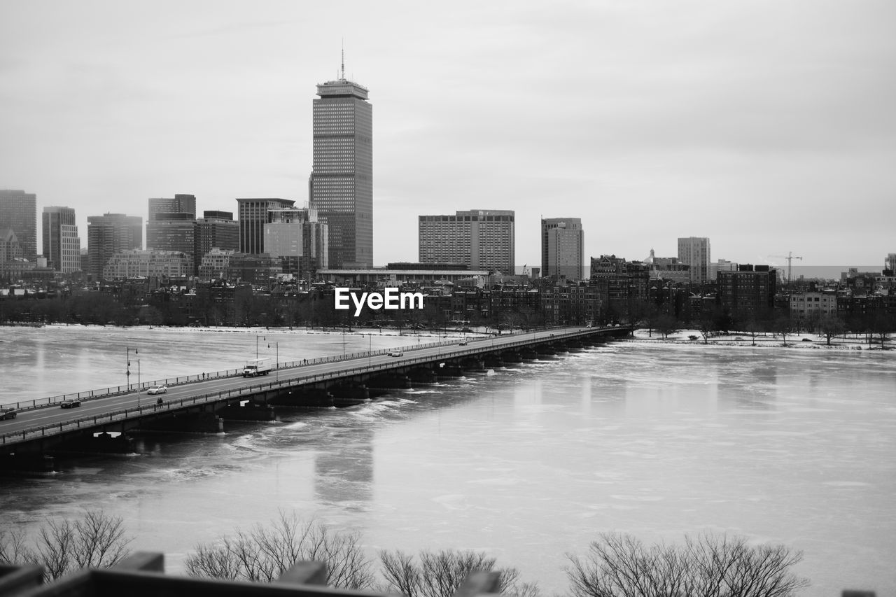 River In City During Winter Against Sky