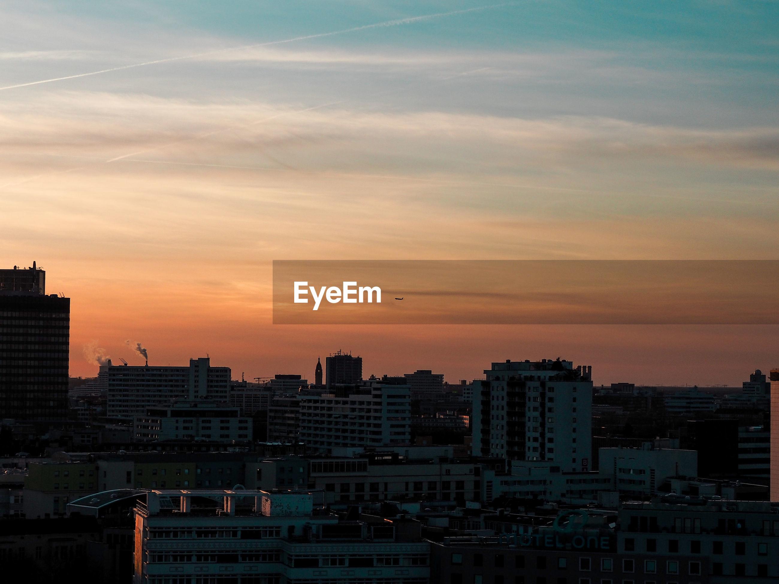 MODERN BUILDINGS IN CITY AGAINST ROMANTIC SKY
