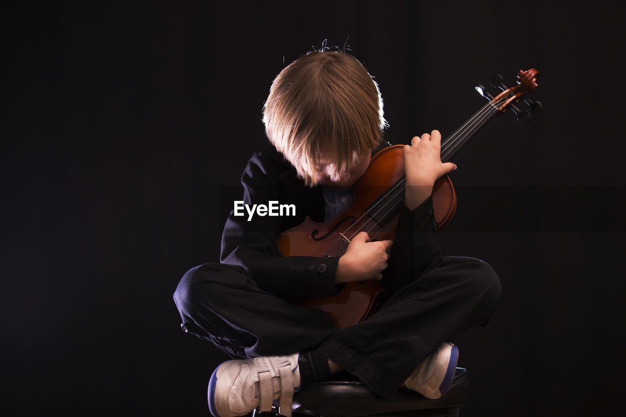 Boy playing violin while sitting against black background