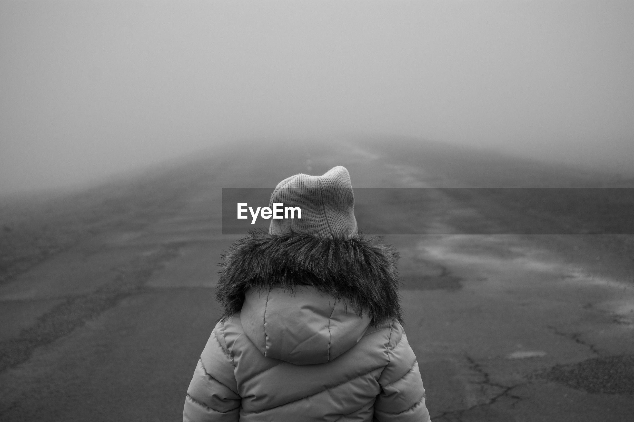 Rear view of girl in fog against sky