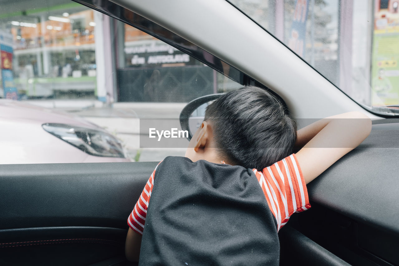 car, motor vehicle, mode of transportation, land vehicle, transportation, vehicle interior, real people, car interior, glass - material, window, lifestyles, one person, transparent, rear view, headshot, men, indoors, travel, leisure activity, males