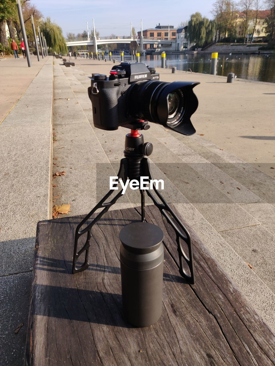 CLOSE-UP OF CAMERA ON TABLE BY STREET IN CITY