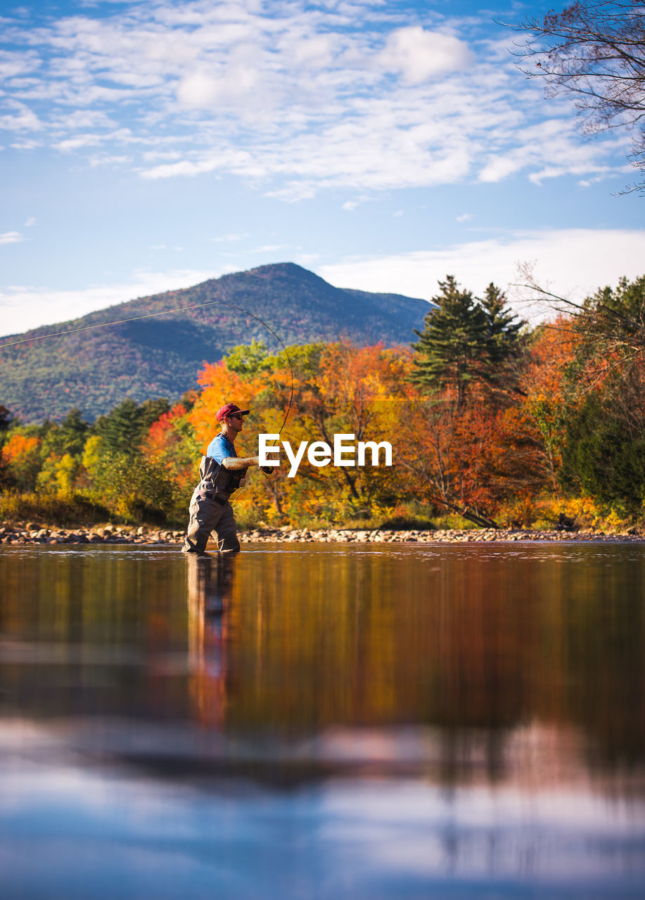 REFLECTION OF MAN ON LAKE AGAINST SKY DURING AUTUMN