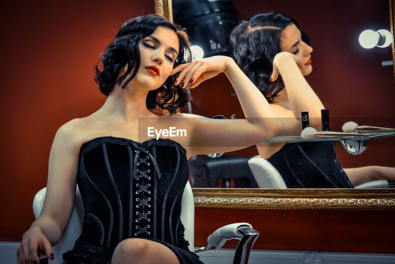 Beautiful Woman Wearing Corset Sitting With Eyes Closed By Mirror