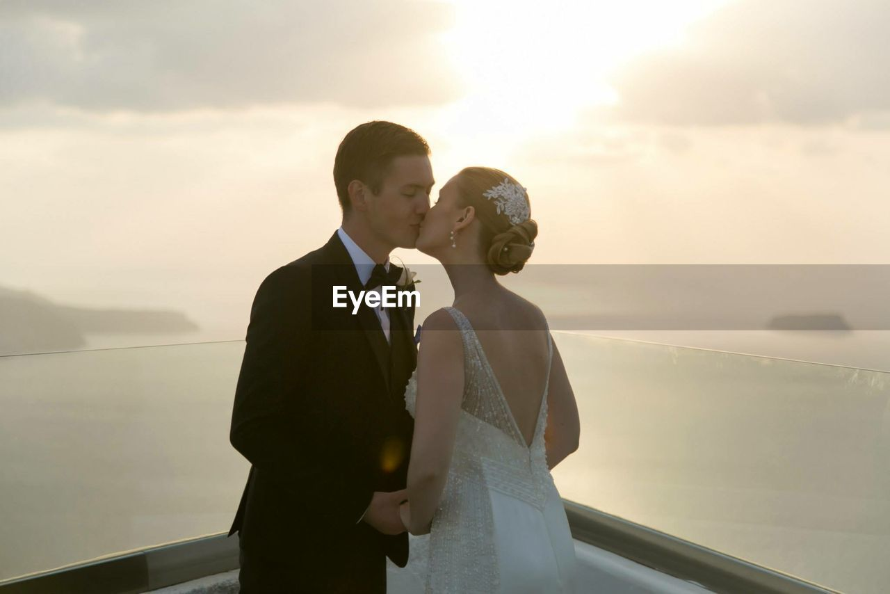 Bride And Groom Kissing At Balcony Against Sea During Sunset