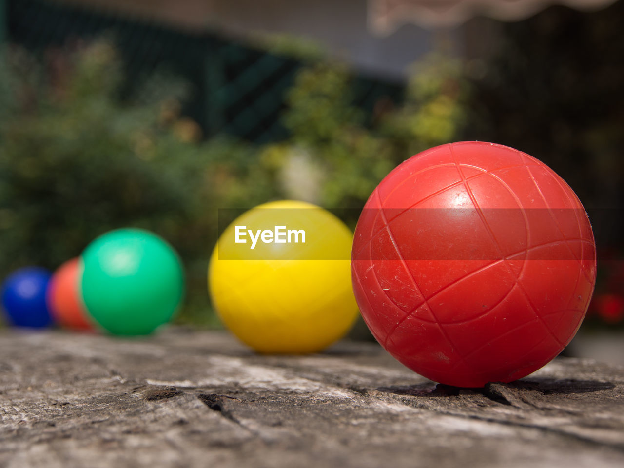 multi colored, red, sphere, selective focus, ball, still life, celebration, table, close-up, no people, wood - material, focus on foreground, day, yellow, indoors, shape, holiday, balloon