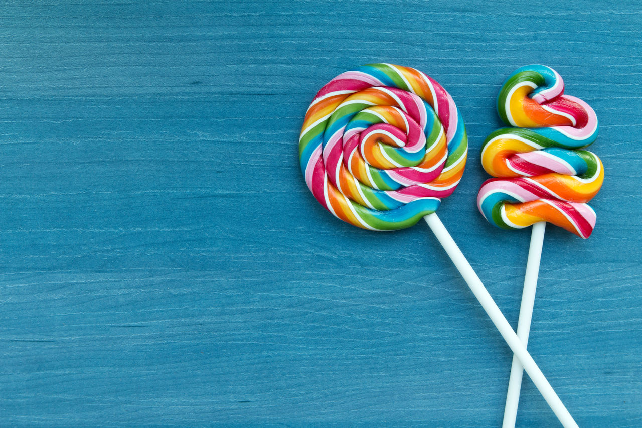sweet food, multi colored, sweet, lollipop, unhealthy eating, indulgence, still life, food, temptation, food and drink, candy, indoors, close-up, no people, table, freshness, blue, dessert, high angle view, ready-to-eat, snack, blue background