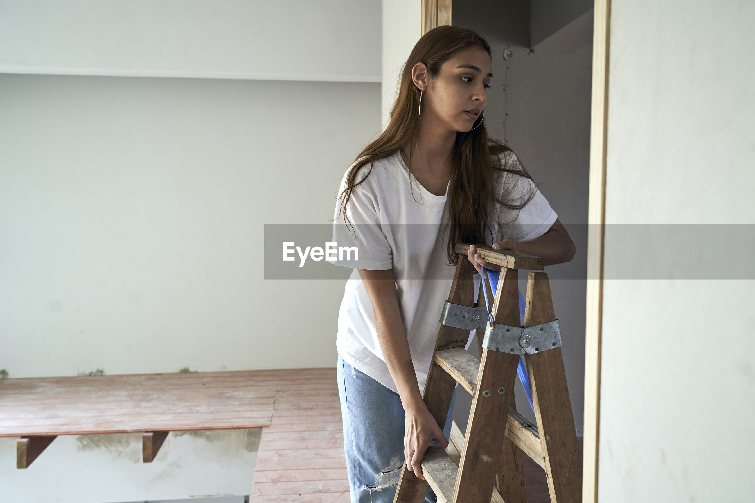 YOUNG WOMAN STANDING IN FRONT OF LADDER AT HOME