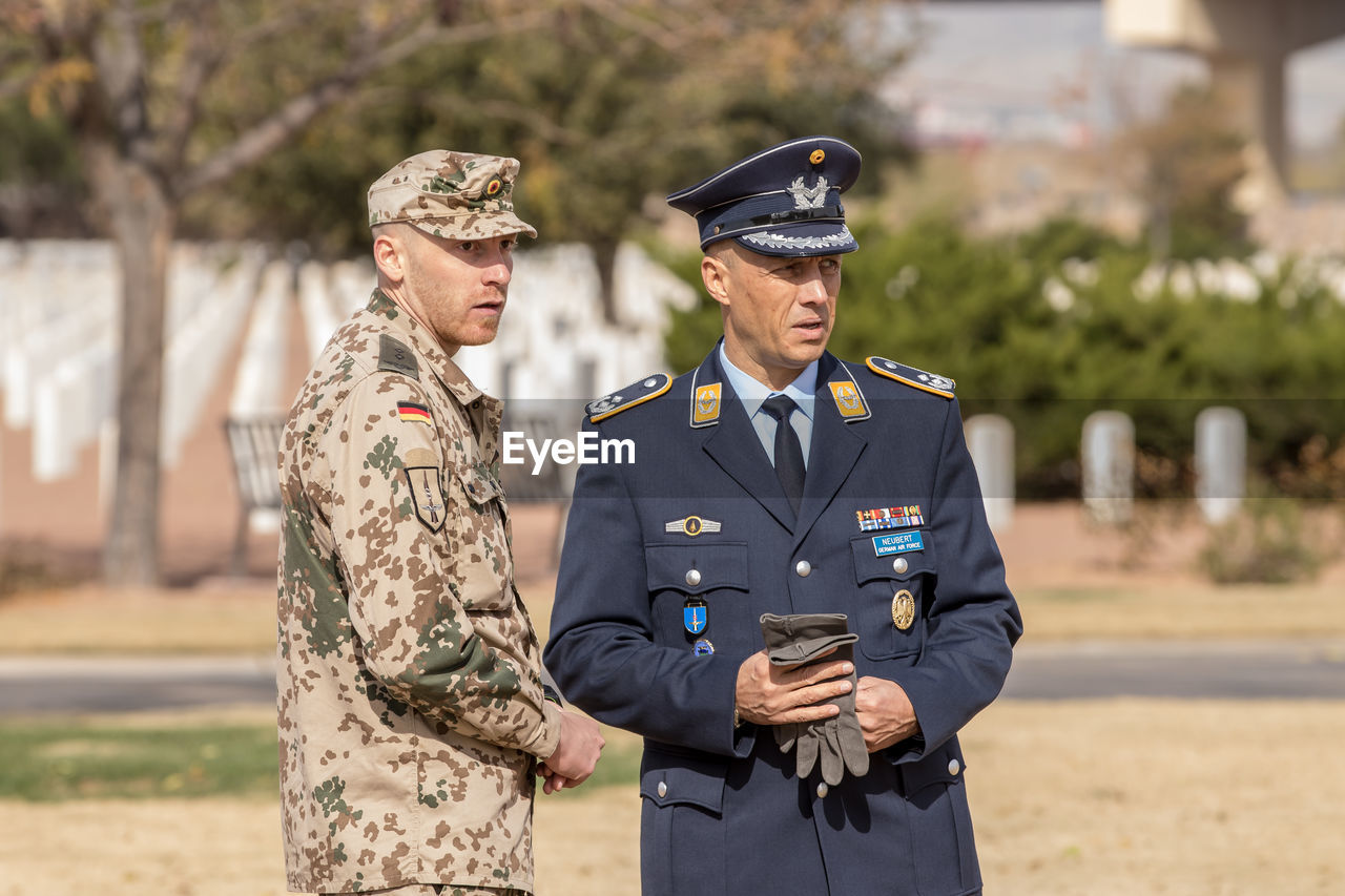 clothing, two people, uniform, military, standing, government, armed forces, military uniform, men, real people, army soldier, young adult, focus on foreground, day, adult, three quarter length, people, protection, security, outdoors, heroes, badge