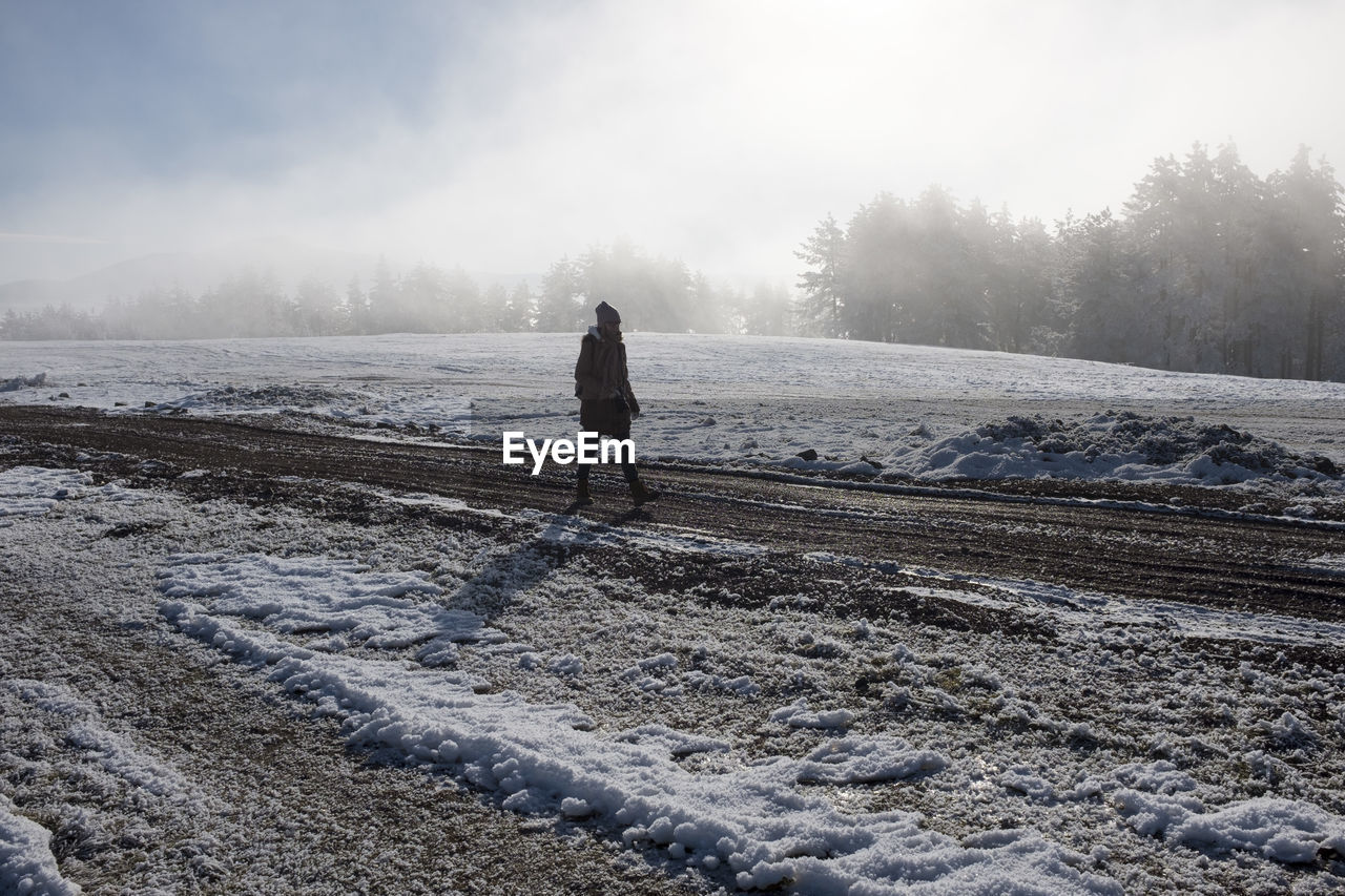 Woman Walking On Snow Covered Field Against Sky