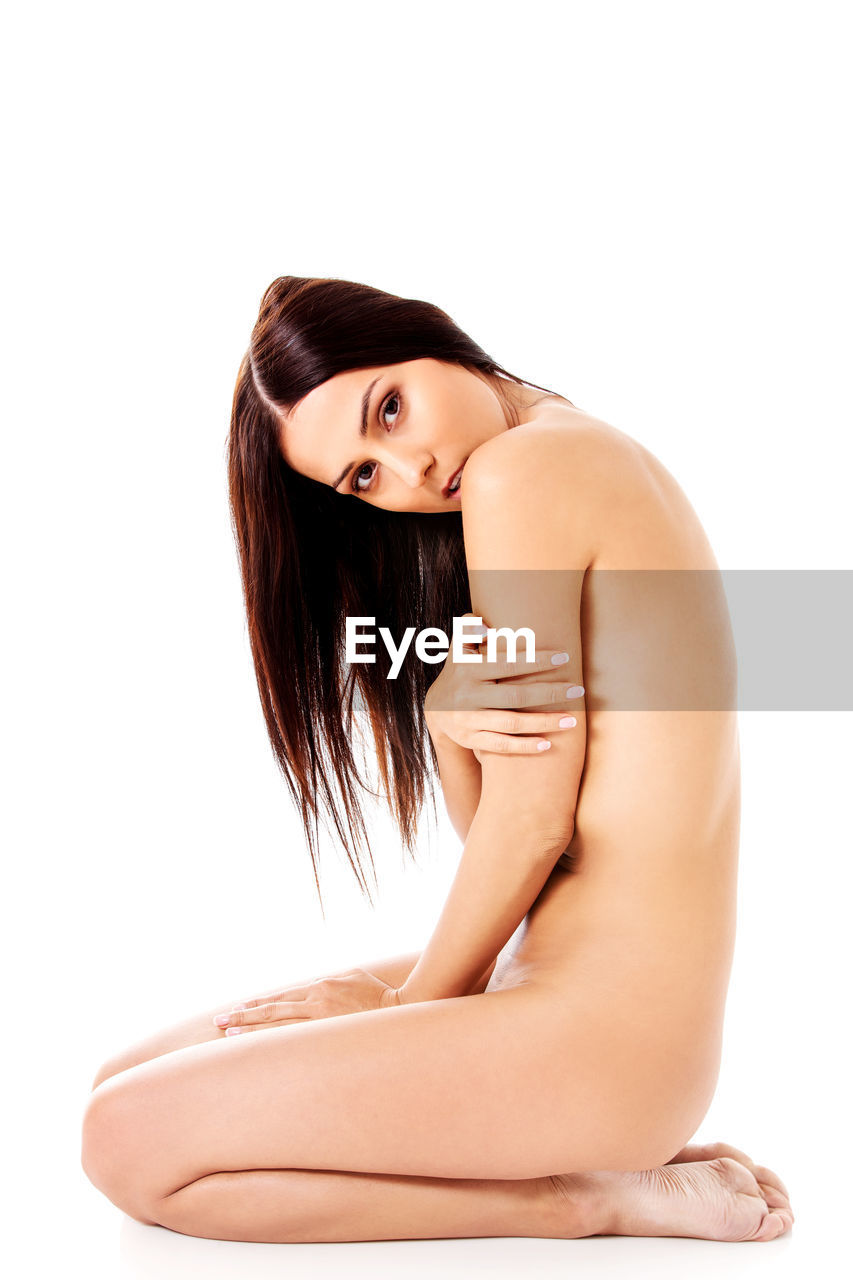 Portrait of naked woman sitting on white background