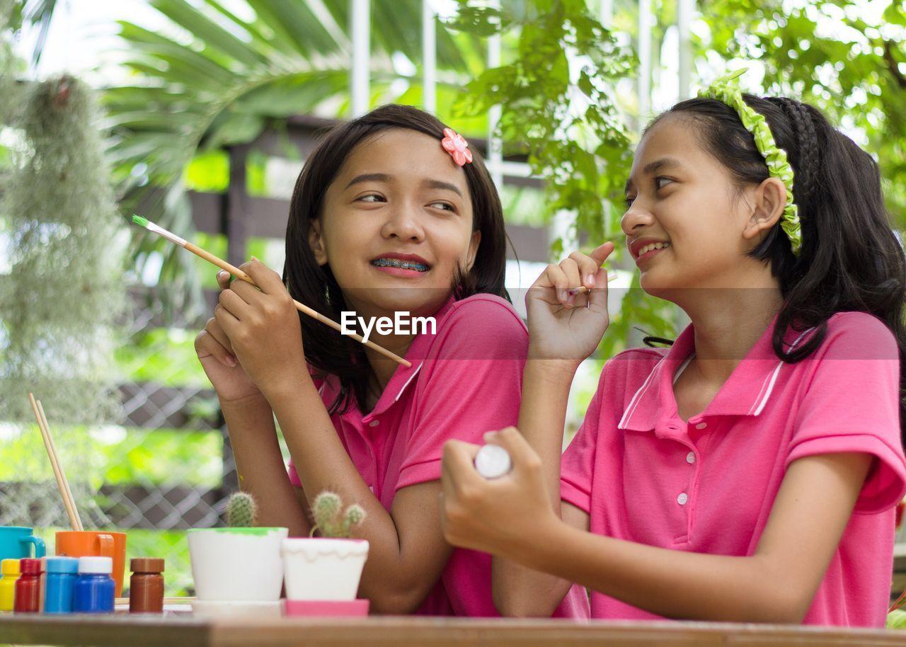 Smiling girls sitting at table