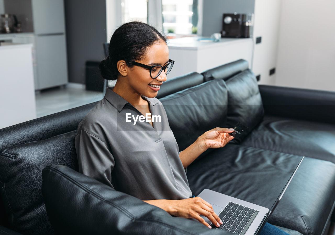 Smiling woman using laptop while sitting on sofa