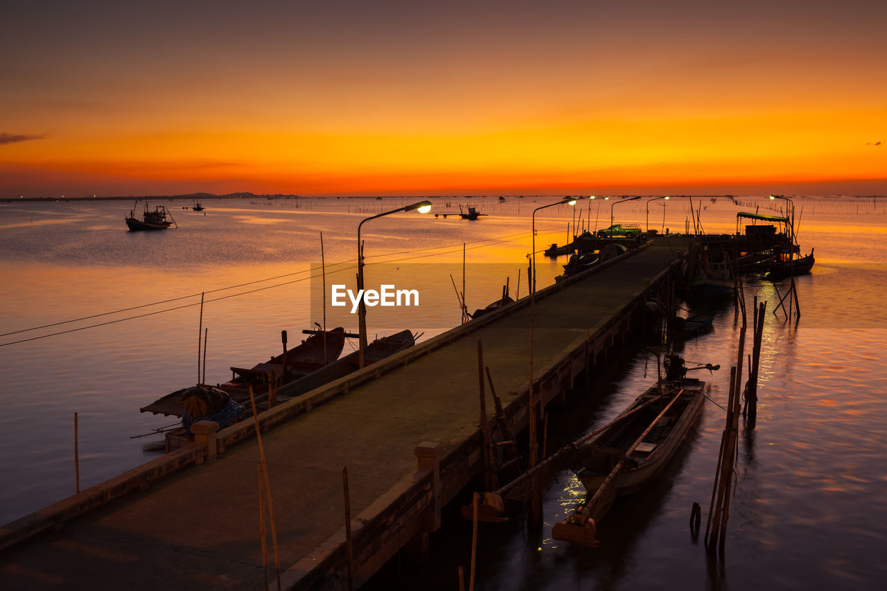 HIGH ANGLE VIEW OF PIER ON SEA AGAINST ORANGE SKY