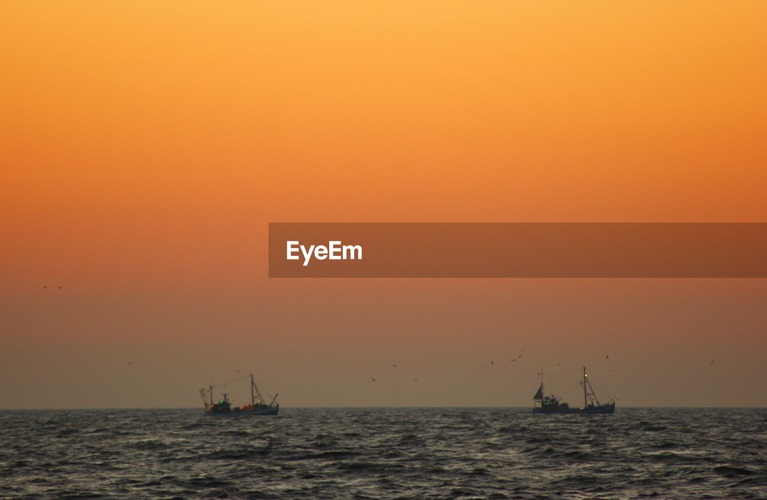 SHIP SAILING IN SEA AGAINST SKY DURING SUNSET