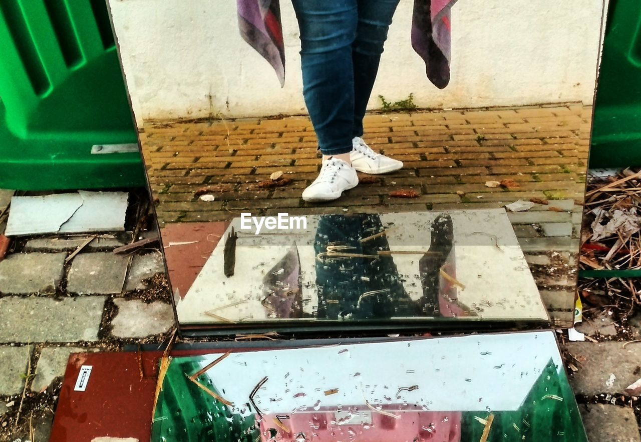 low section, human leg, day, standing, body part, real people, human body part, people, city, men, outdoors, water, street, lifestyles, shoe, footpath, architecture, two people, nature, human foot, messy
