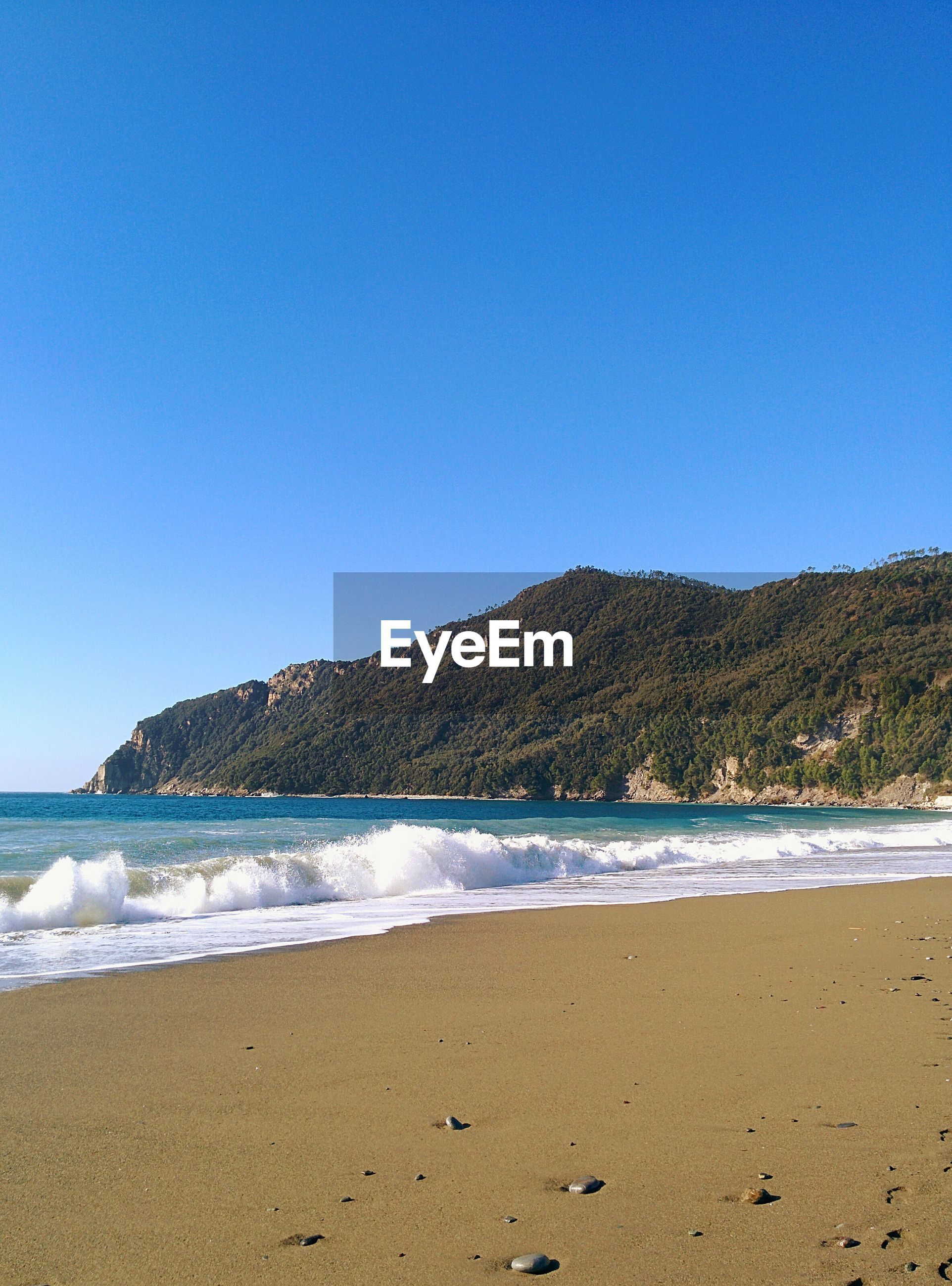 clear sky, water, copy space, blue, tranquil scene, mountain, scenics, tranquility, beach, sea, beauty in nature, shore, nature, sand, idyllic, coastline, non-urban scene, mountain range, day, outdoors
