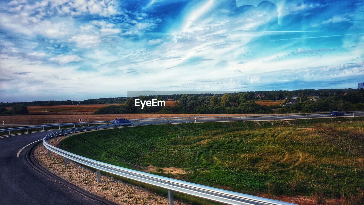 cloud - sky, sky, transportation, road, nature, no people, landscape, plant, environment, grass, day, beauty in nature, tranquility, curve, land, city, scenics - nature, outdoors, tree, field, crash barrier, multiple lane highway