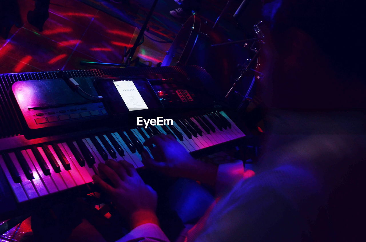 LOW ANGLE VIEW OF MAN PLAYING PIANO AT NIGHTCLUB