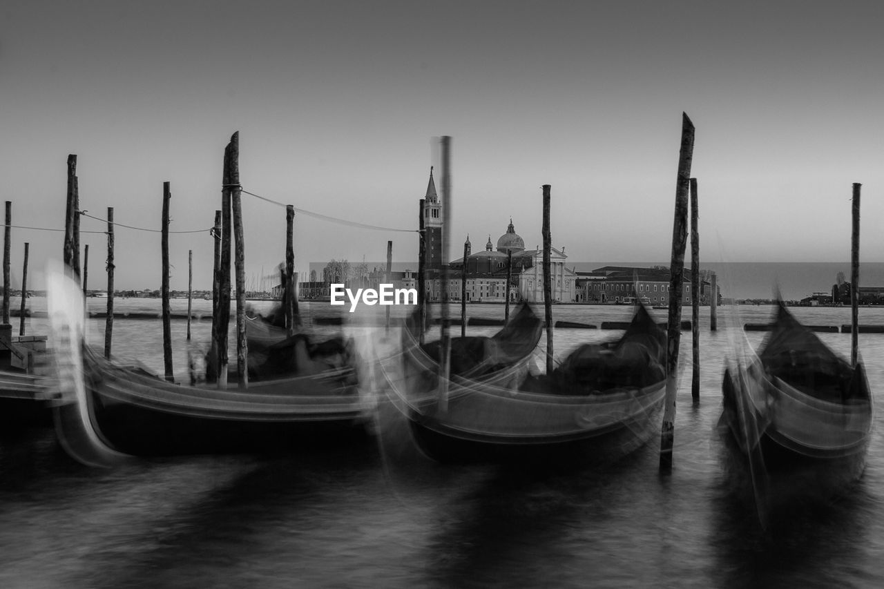 nautical vessel, transportation, sky, water, mode of transportation, gondola - traditional boat, clear sky, architecture, nature, no people, built structure, travel, blurred motion, building exterior, moored, waterfront, outdoors, travel destinations, wooden post
