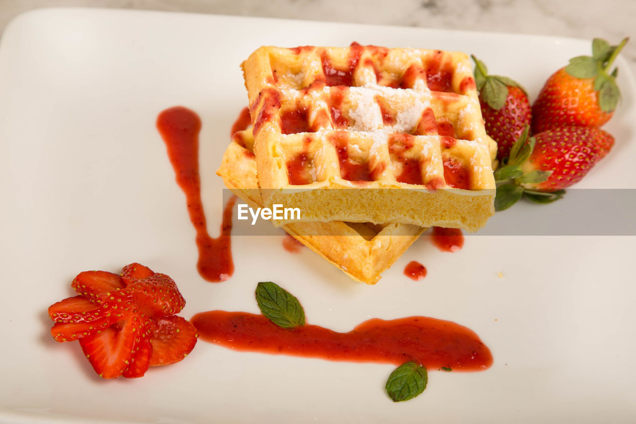 Close-up of waffles with strawberries served in plate