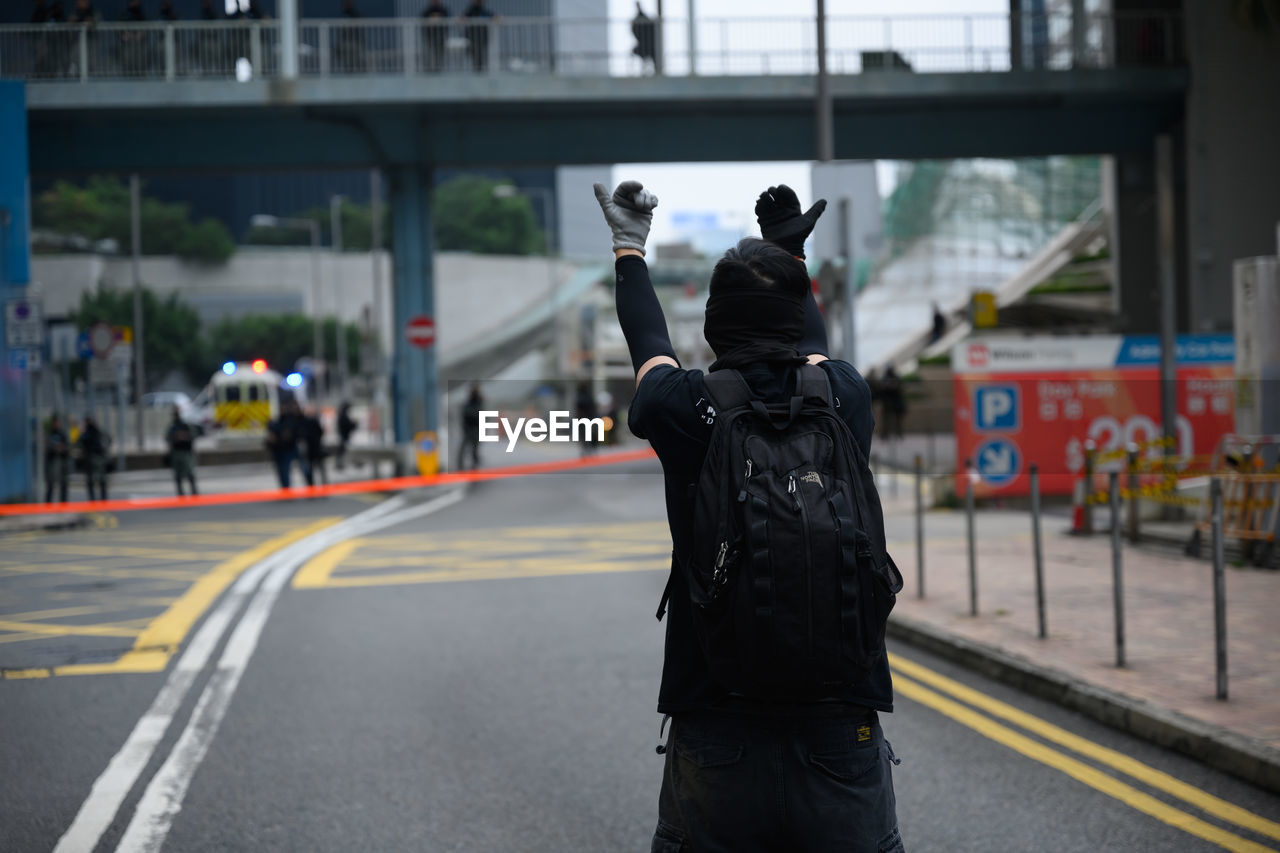 Rear view of man protesting on street in city