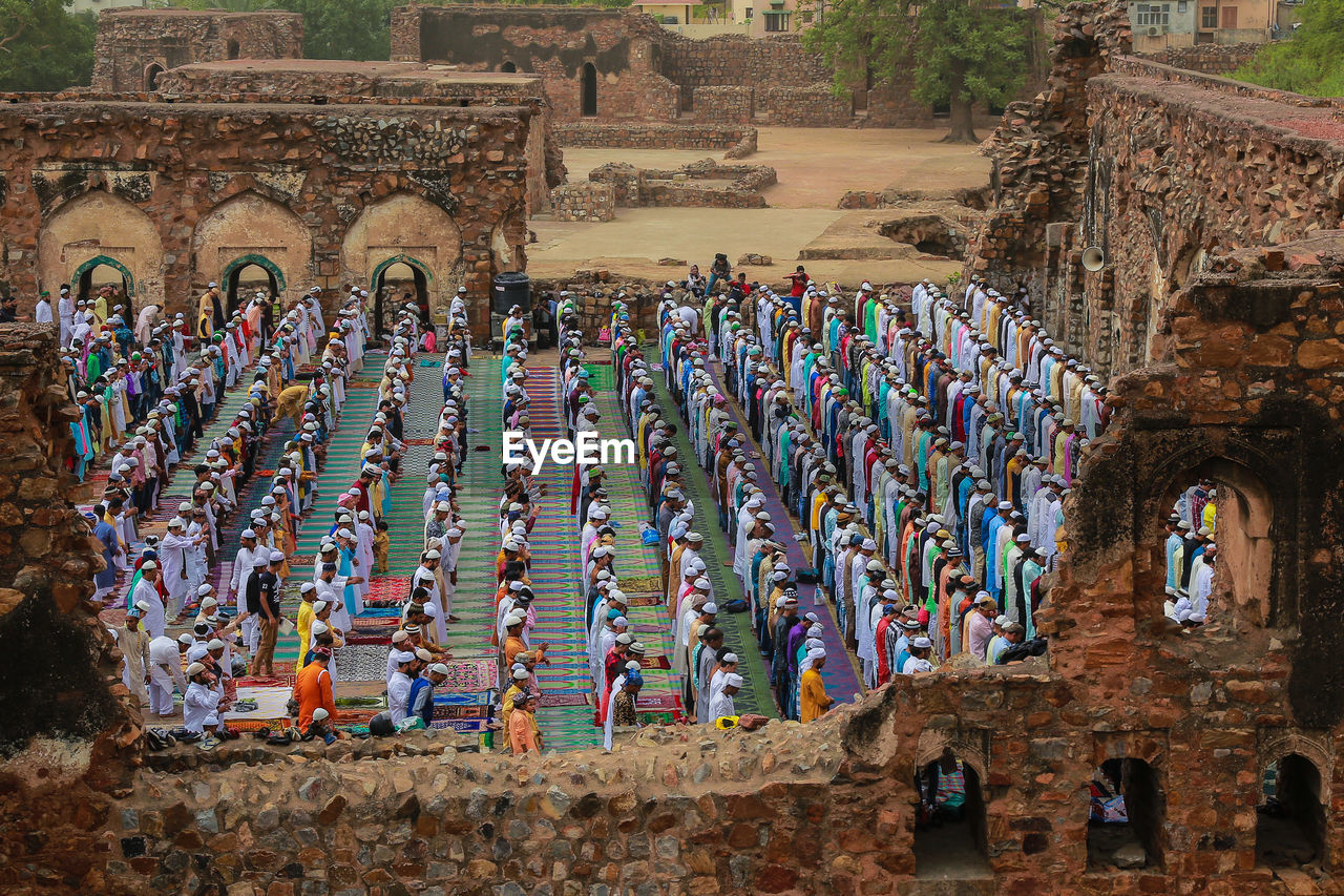 Muslims pray as others take part in eid al-fitr prayers in the ruins of the feroz shah kotla