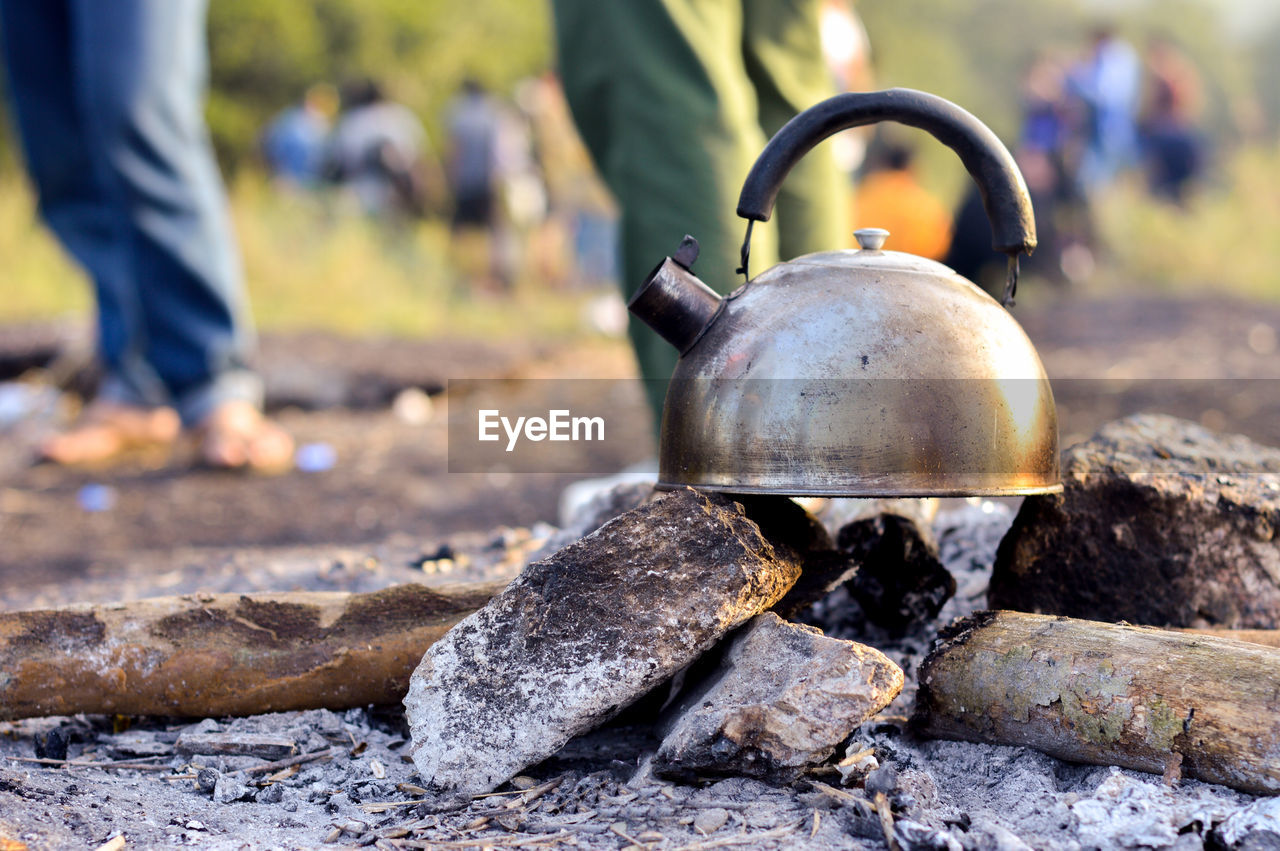 Kettle On Stones With People On Field In Background