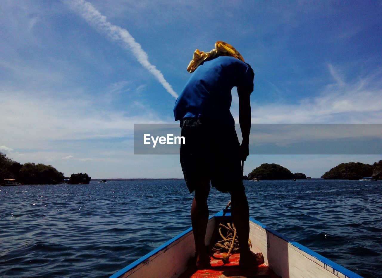 Full length rear view of man on fishing boat in sea
