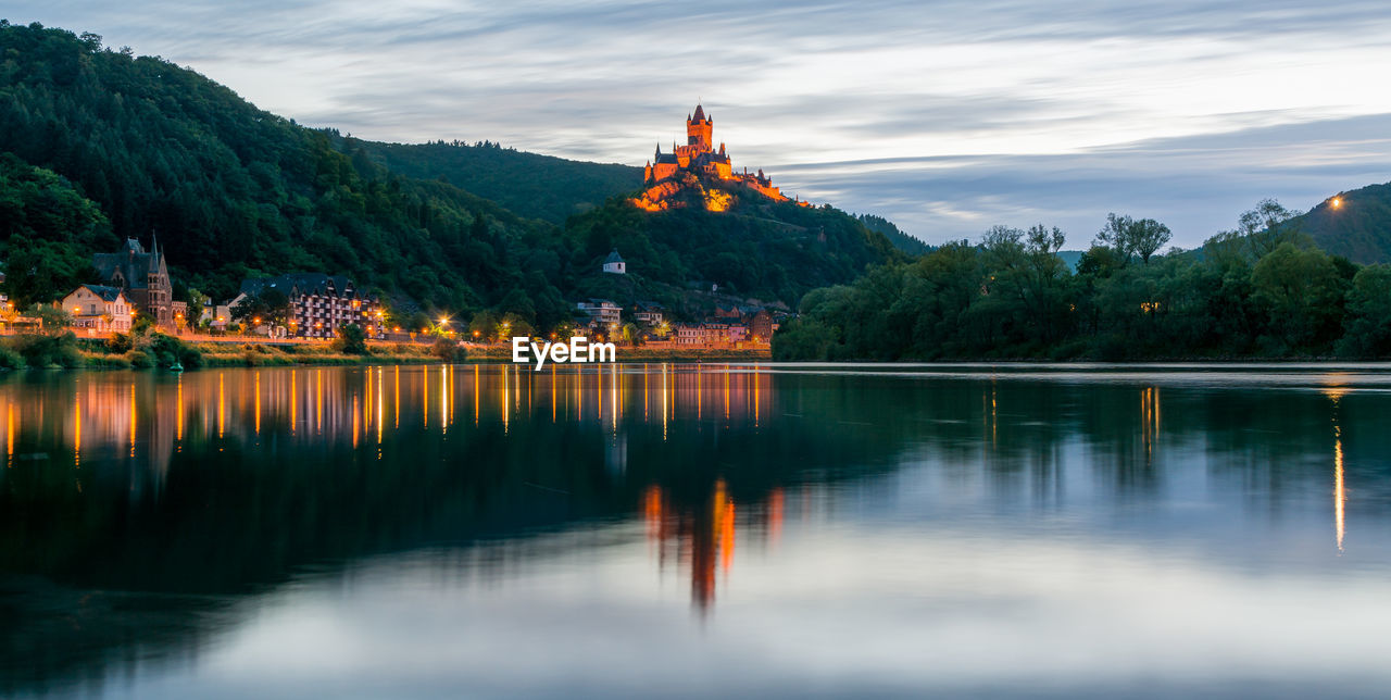 Scenic view of cochem imperial castle on mountain reflecting in river at dusk