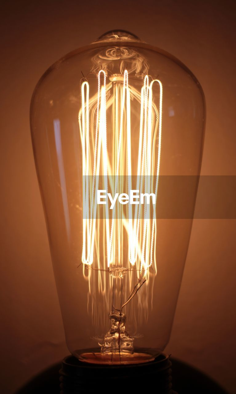 lighting equipment, illuminated, light bulb, electricity, glass - material, indoors, glowing, filament, close-up, light, transparent, electric light, light - natural phenomenon, no people, fuel and power generation, studio shot, orange color, technology, single object, dark, glass, black background, electrical equipment