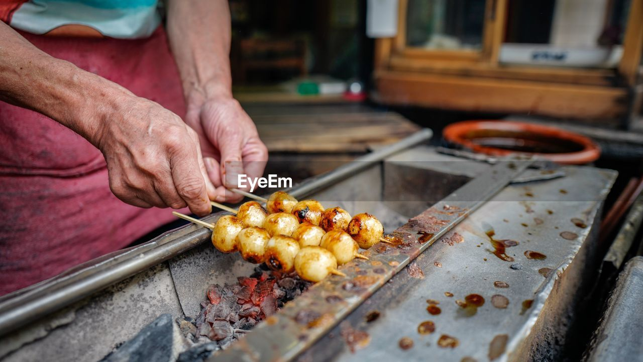 Midsection Of Vendor Cooking Dumplings Over Coal At Market Stall