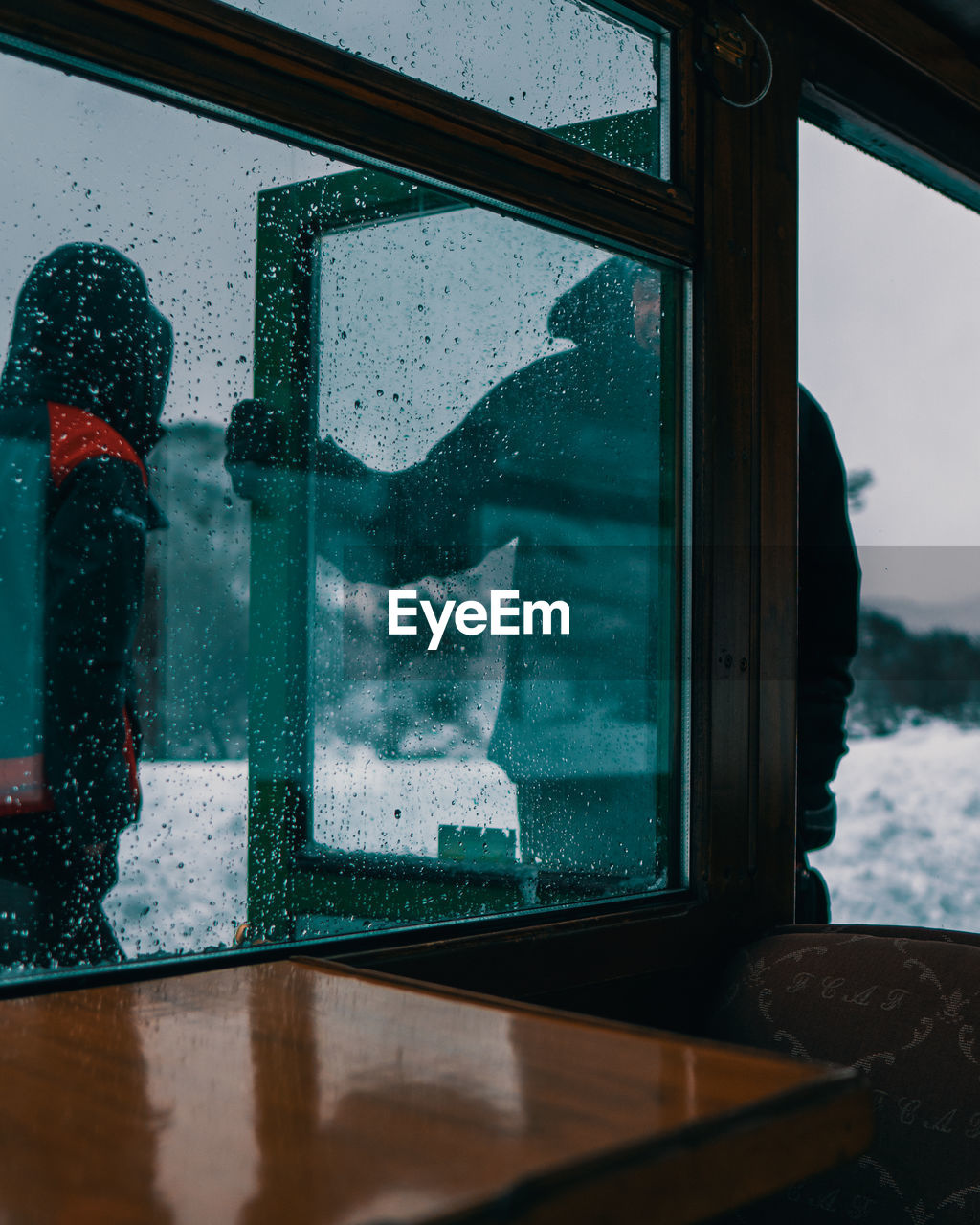 Men seen through window during winter