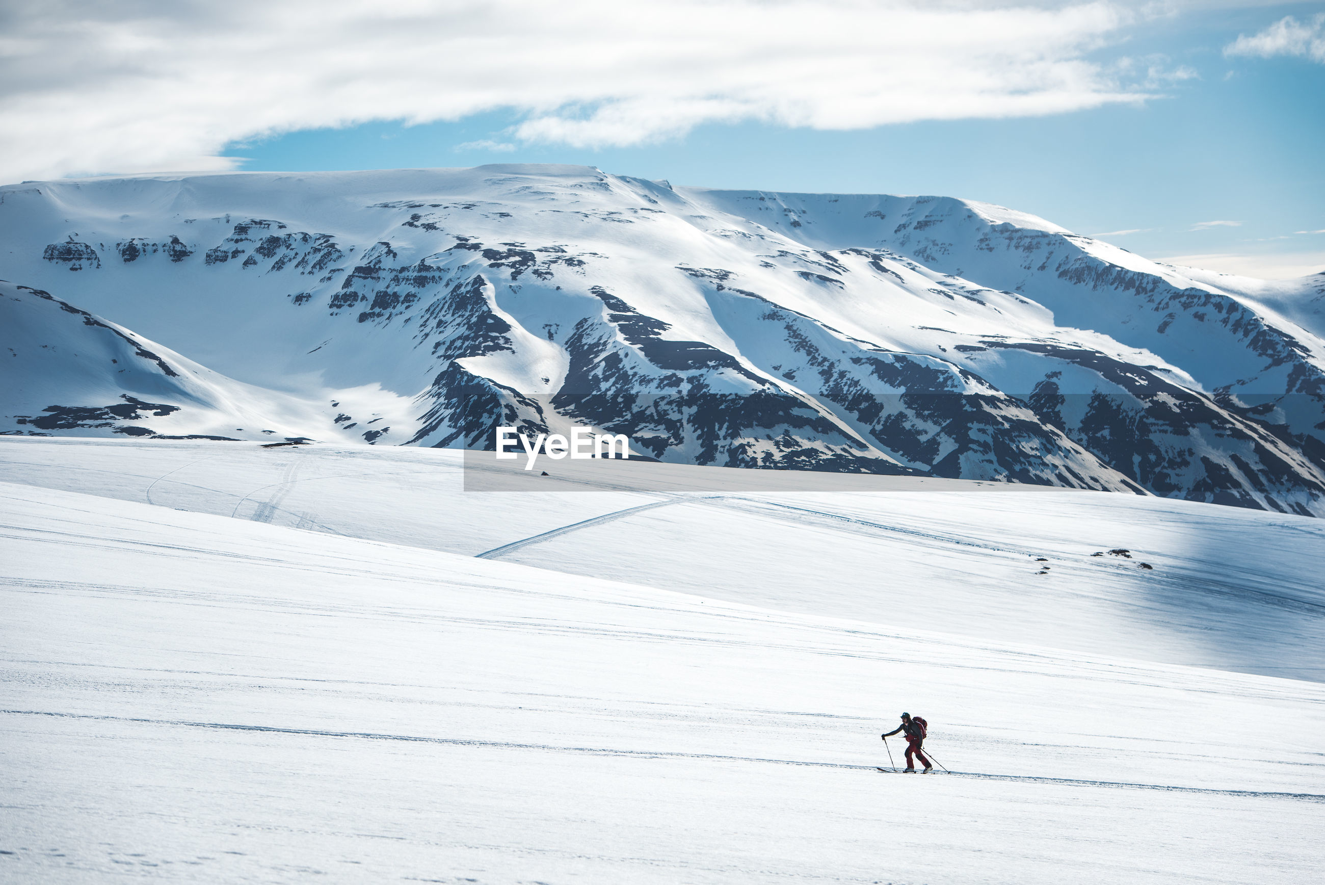 PEOPLE SKIING ON SNOWCAPPED MOUNTAINS AGAINST SKY