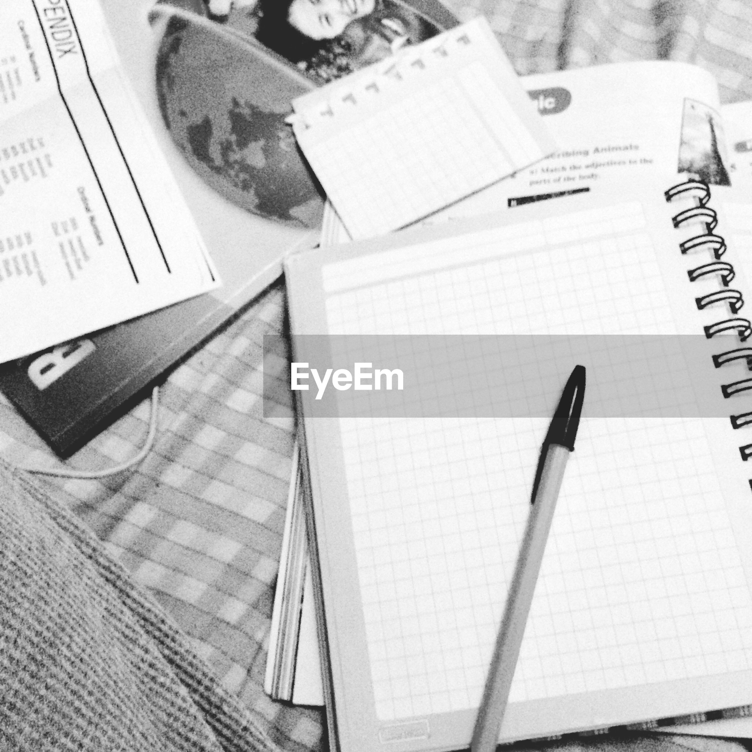 indoors, communication, book, high angle view, education, table, text, paper, technology, close-up, still life, pen, wireless technology, western script, page, no people, connection, document, arts culture and entertainment, wood - material