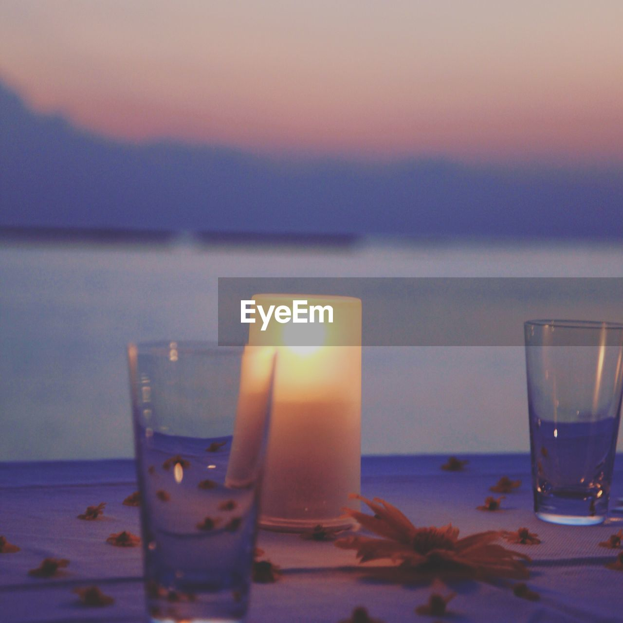 water, sunset, table, candle, sea, burning, flame, no people, nature, horizon over water, close-up, sky, tranquil scene, illuminated, drinking glass, beach, indoors, beauty in nature, drink, flower, scenics, day