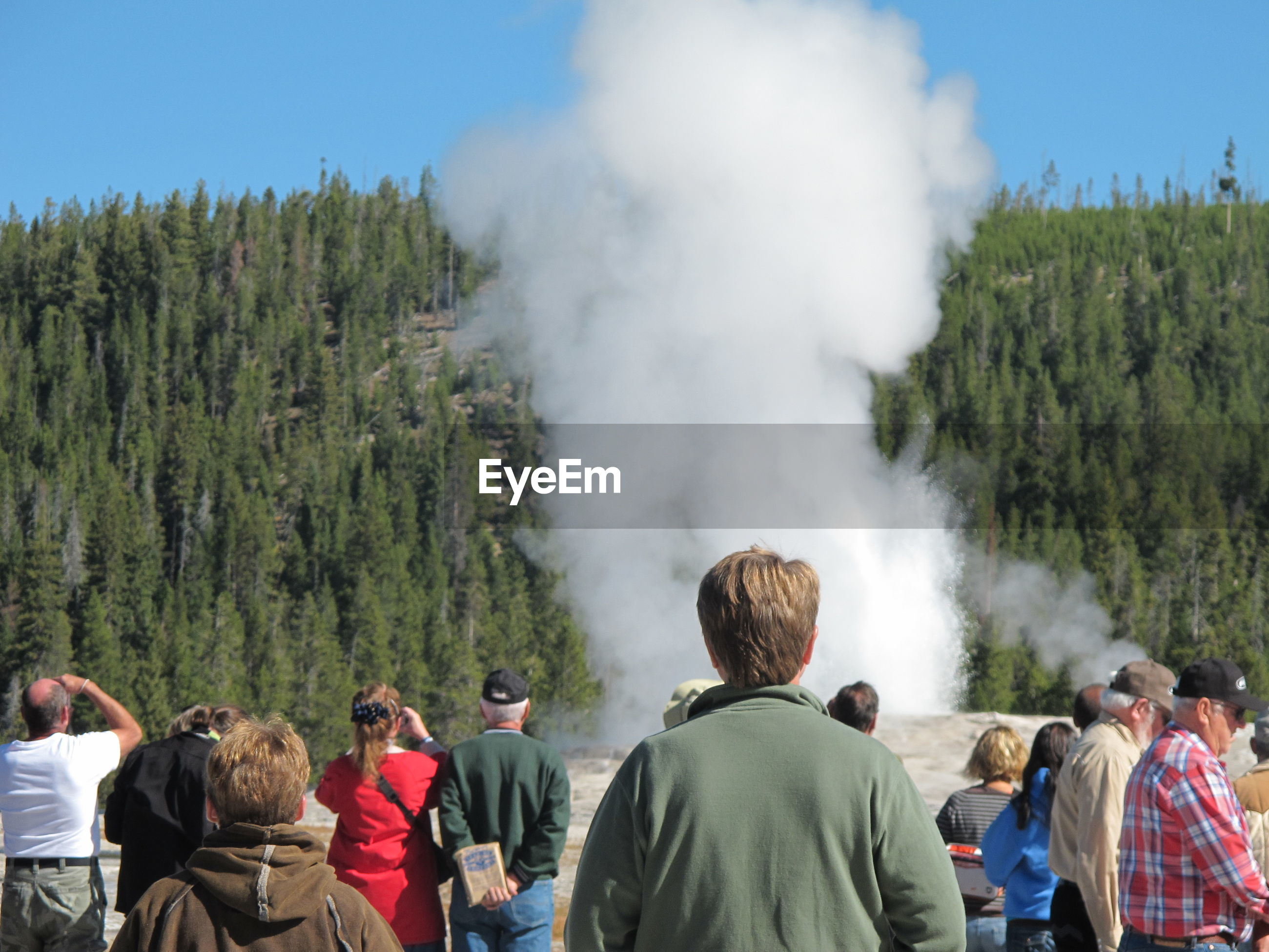 Rear view of people standing by steam emitting from field