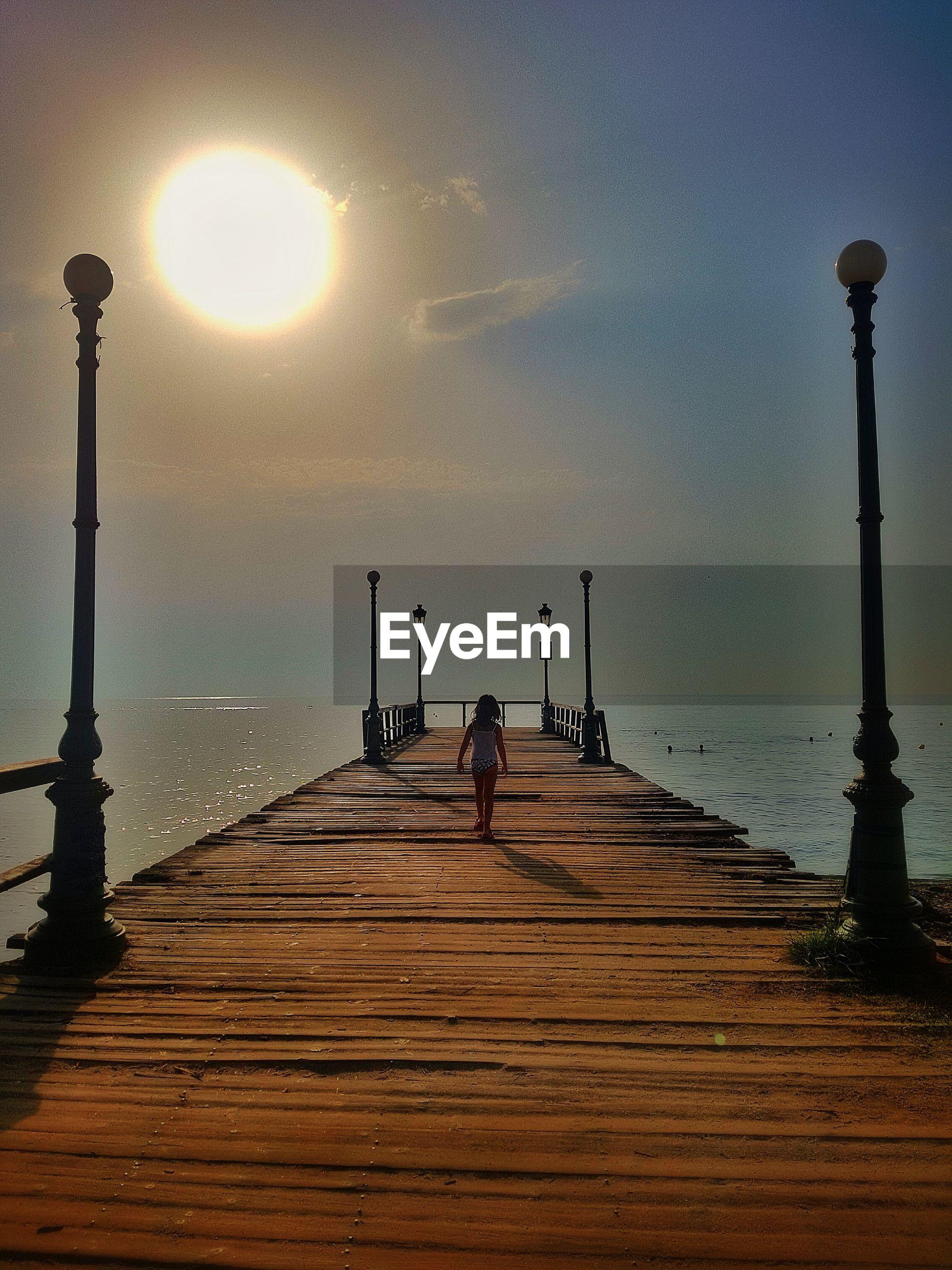 Rear view of girl walking on pier against sky