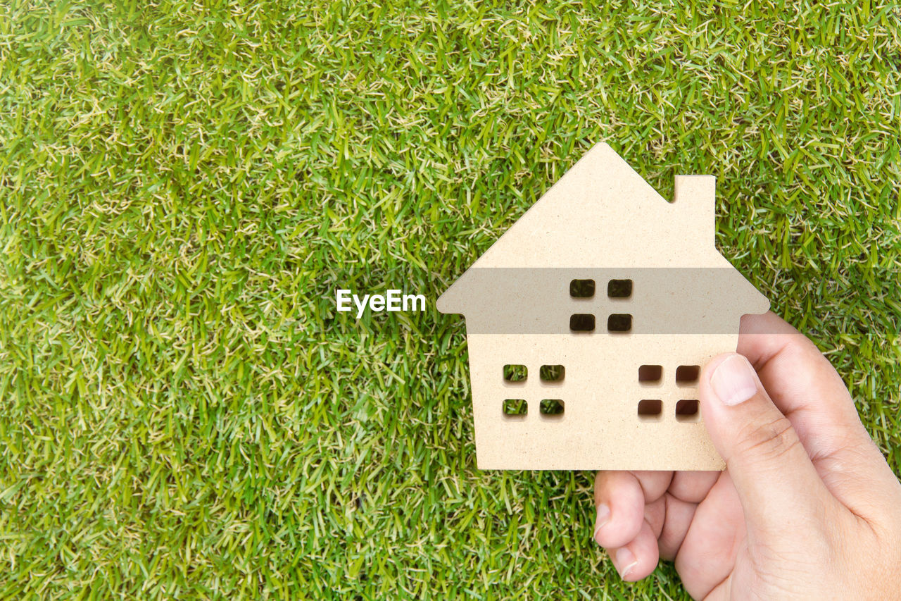 grass, home ownership, human body part, house, human hand, outdoors, architecture, model - object, day, puzzle, real people, one person, people