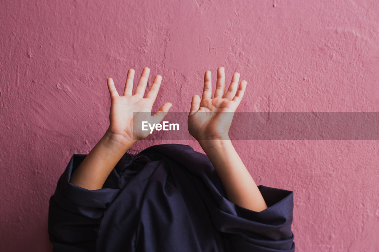 wall - building feature, real people, human hand, hand, human body part, one person, unrecognizable person, built structure, body part, wall, standing, day, lifestyles, human finger, women, indoors, child, finger, architecture, obscured face, arms raised, purple